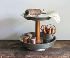An adorable serving stand made from a vintage textile wood spool and vintage pie and cake pans. A small Bake King pie pan is used as the base. The pans are charming, though they are showing some wear with scratches, bits of rust and patina. A wonderful display stand for small foods. Great for the office or craft room to hold supplies. May also be used to show off your vintage glass Christmas ornaments during the holidays. :: 9 1/8 wide x 7 3/4 high {apples and craft supplies ar...