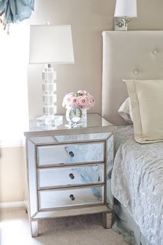 Mirror table, lamp and flowers.