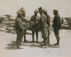 Photograph of the Indian troops examining a fragment of a shell fired by Turkish gun 'Asiatic Annie'. No 2727. From a collection of official photographs of the Dardanelles Expedition, 1915-1916.