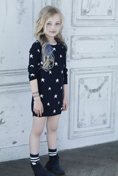 Little girl outfit: black dress with white stars, striped socks and military boots.
