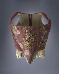 Boned bodice, France 1750-1760. Rose silk with a pattern of flower bouquets in multicoloured silks, back made of crimson damask, linen lining.
