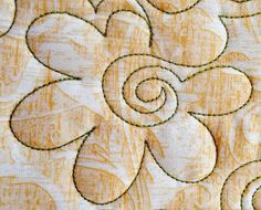 Image from http://quiltsocial.com/wp-content/uploads/roundedflowerwithspiralcentremachinequiltingdesign_69200_q_l.jpg.