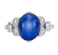 Art Deco Platinum, Cabochon Sapphire and Diamond Ring   One oval cabochon sapphire ap. 5.20 cts., 6 half-moon shaped diamonds, c. 1920, ap. 3 dwt. Size 7.