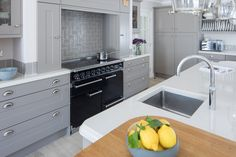 The Falcon range cooker with induction, framed with an oak mantel and practical worktop storage was the perfect feature to style from Integrated appliances concealed behind unit doors never reveal their age over time and glass doors visually open up the kitchen bringing more light to the space. - Falcon 1092 Deluxe cooker in Black