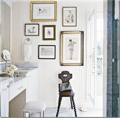 small white bathroom with make up vanity, stool, and gallery wall with figure paintings and drawings... Small Bathroom Chic: Artwork Brightens Bathroom Space from Bathroom Bliss by Rotator Rod
