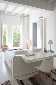 Bem clean e moderno, mas muito aconchegante, este quarto apostou na mistura entre branco e as tonalidades de azul. No centro, a cabeceira foi integrada à mesa de trabalho e também abriga luminárias.
