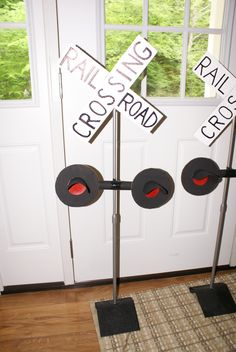 Train crossing signs made with cardboard, cardstock, glitter and paint.  These are attached to speaker stands for a train party decoration.