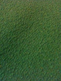 Dark green fabric with bumpy texture on one side. polyester? 2 way stretch medium weight 5 yards or so, a chuck is cut out of the last yard