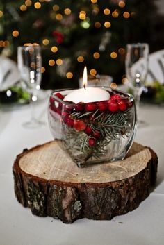 cranberry and greenery centerpiece on slice of tree trunk