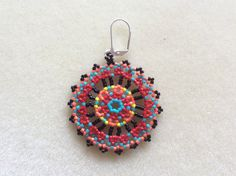 Name: The Eye Catcher Mandala Beaded Earrings Size: 2 1/2 inches long ( with hooks) 2 inch wide Colors: Black, turquoise, red, yellow, and coral   I have been beading for 20 years and I hope my experience shows through my work. For me, this is soul satisfying work and I hope my creations carry within it the energy and love I have put into them. I only use use high quality materials. I used size 11 size seed beads , Nymo beading thread so your earrings will last for years and years. I als...