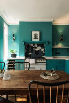 Teal walls and cabinet, white ceiling, crown and counter, inventive stove backsplash, lighting all juxtaposed with antique farm table.
