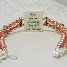 This vintage style bracelet has copper colored Swarovski pearls, and holds a two-sided photo charm with a photo on one side, and a custom text image on the other.