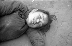A starving Chinese woman, too weak to stand, lies on the barren ground with blades of grass protruding from in her lips;a desperate attempt to find nourishment during the Henan famine. Henan Province was hit by alarge-scale famine between the summer of 1942 and the spring of 1943 that led to the death ofthree million people. -Henan Province, Republic of China. November 1942. Image taken by Theodore H. White.