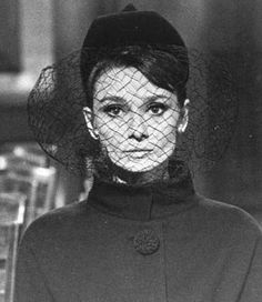 """thefashionofaudrey:  The actress Audrey Hepburn as Regina Lampert and photographed by Vincent Rossel at theStudio de Boulogneduring the filming of """"Charade"""". Paris (France), November 1962. Audrey was wearing: Suit:Givenchy(of black wool, jacket with buttons coated with black wool pompoms and skirt, of his collection for the Autumn/Winter 1962/63). Hat:Givenchy(model pillbox lined with black velvet with a small veil, created especially for her wardrobe in this film)."""