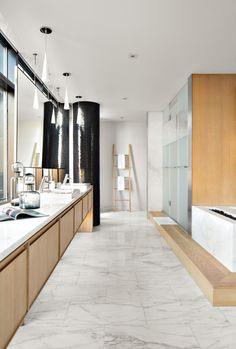 A rift-sawn oak vanity in the master bath faces a soaking tub clad in Calacatta Gold marble.