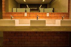 O concreto aparente na fachada equilibra as cores do exterior e valoriza as esquadrias desalinhadas. Piso de cimento queimado, paredes de tijolinho, telha metálica e teto revestido com chapas de compensado dão aconchego. Nas salas, a estrutura metálica foi mantida e restaurada para agregar valor ao conceito industrial aplicado ao projeto, remetendo os antigos galpões e lofts nova-iorquinos. #arquitetura #architecture #interiors #design #tijolinho #brick #concreto #banheiro #bathroom…
