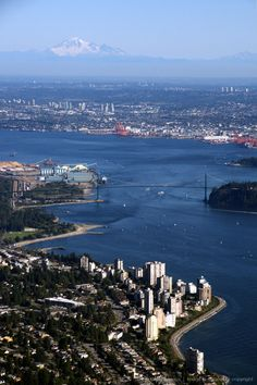 West Vancouver in the foreground, Ambleside Park and Beach under the Lions Gate Bridge and the Burrard Inlet, looking east with Washington's Mount Baker...
