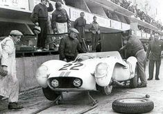"""Ed Hugus's LucyBelle II in the pits at Le Mans, 1958. Hugus is on the pit wall at left, co-driver Erickson at right. """"It rained and hailed during my stint,"""" recalled Hugus."""