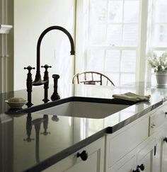 Kitchen Island Sink              This island, which houses the sink, features a honed-granite countertop that recalls the matte look of soapstone, a surface common in old farmhouse kitchens. The sink's high faucet makes it a breeze to wash any large pans or dishes while the square shape of the sink creates clean lines that mesh with the rest of the kitchen