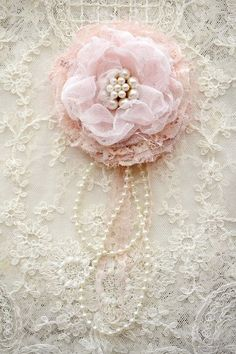 Idea for corsage - layer fabric and lace rosettes, add old ear-ring or pearls for centre and adhere bead strand and/or thin ribbon tails at back. :)