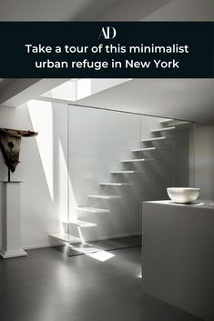 The lofty apartment is made up of three adjacent duplex units, each with access to a rooftop terrace.   #soothing #minimalist #monochrome #glass #gray #NewYorkCity #entry #stairs #stairway #cement #concrete #art #sculpture #spacious #loft #neutral #white #modern
