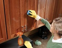 To clean cabinets, First heat slightly damp sponge/cloth in microwave for 20 – 30 sec. until it's hot. Put on a pair of rubber gloves, spray cabinets with an all-purpose cleaner containing orange oil, then wipe off cleaner with hot sponge.