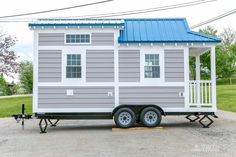 Tiny house with a blue roof and grey siding.