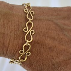 I love this.  Hopefully it will look better on my arm.  Gold charm bracelet Hand forged S links 14K gold filled.  Size 7. $45.00, via Etsy.