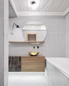 Architecture firm @formafatal chose a minimalist industrial palette for the renovation of this maisonette bathroom in Prague. The bathroom is surfaced in white mosaics from Hisbalit, and a brass washbasin from Morocco is flanked by a Tolomeo Micro Parete lamp from Artemide.  #bathroom #interior #renovation #modern #dwell  Photo by @boysplaynice  Architecture by Dagmar Stepanova of @formafatal Location: Prague, Czech Republic