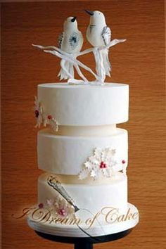 Unique white art deco three tier winter or christmas wedding cake decorated with snowflake motifs