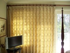 Wall of windows and doors with lots of sun.  Embroidered draperies hung on a decorative rod and rings.