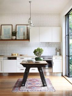 Art and an antique table and vintage rug in a classic meets modern kitchen with recessed panel white cabinets, open wood shelving with a leaning gallery wall, white square tiles, a bonsai tree and doors leading to the patio outside.
