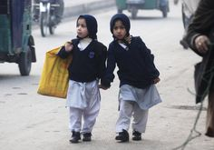 Photos of the day - January 12, 2015 : Girls carry their school bags as they walk along a road while heading to their school after it reopened in Peshawar January 12, 2015. (REUTERS/Khuram Parvez)