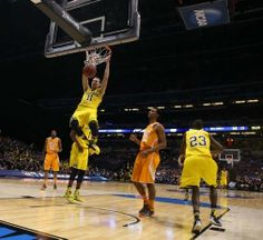 Michigan's Nik Stauskas scores against Tennessee's Derek Reese during first half action of the NCAA Midwest Regional Tournament game on Friday, March 28, 2014, at Lucas Oil Stadium in Indianapolis, Indiana.