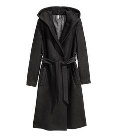 Musta. CONSCIOUS. Hupullinen ja vuorillinen takki huovutettua villasekoitetta. Piilopainonapitus edessä ja solmittava vyö. Sivutaskut ja takahalkio. Takin
