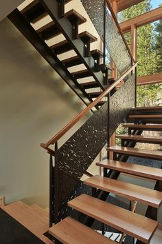 A winding staircase boasts a custom perforated metal rail. The modern-rustic home features glass walls framed by natural wood, allowing it to take advantage of sweeping views of woods and mountains.