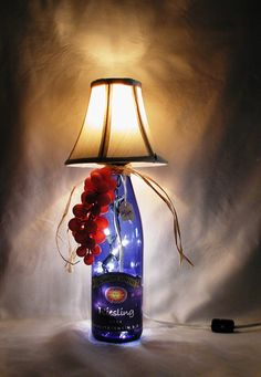 """WINE BOTTLE LAMP.  This striking wine bottle lamp is made from a recycled Schmitt Sohne Reisling wine bottle.  The bottle is cobalt blue and the lamp shade is cream.    Lamp is approximately 15"""" tall and approximately 7 """" wide.  It has a nite light under the shade and mini lights inside the bottle.  Comes with a long, switched cord for convenience.    Beautiful appearance - on or off.    Great for a corner, counter top, bar - anywhere some soothing ambiance is needed.  $30.00"""