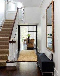 Dark hardwood flooring. Runner on stairs. Large mirror. I want this foyer.