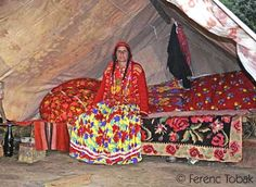 A Gypsy woman sitting inside her tent. She is in full color – the lemon color in her skirt is a newer fashion than the more traditional red-based patterns.