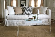 White slipcovered sofa, natural fiber rug, lucite coffee table. Casual and elegant.