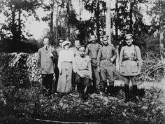 Nicholas II, Imperador da Rússia, sua filha Grã-duquesa Anastasia Nikolaevna, Príncipe Vasily Dolgorukov, Franz Juravsky, Tchemodurov e dois outros agentes do sexo masculino em Tsarskoye Selo. O grupo está em pé em uma floresta com árvores atrás deles e uma pilha de madeira cortada para a esquerda. Nicholas II está sentado na frente do grupo com sua filha Grã-duquesa Anastasia de pé ao lado dele para a esquerda. Em 1917.
