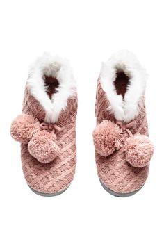 Pantofole in maglia: Pantofole in morbida maglia. Alte alla caviglia con bordo in finta pelliccia e fiocco decorativo con pon-pon in pelliccia sintetica alle estremità. Fodera e soletta in tessuto tipo pelliccia. Suola morbida in finto camoscio con gommini antiscivolo.