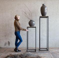 Grote aarderwerk vazen op hoge plantentafels
