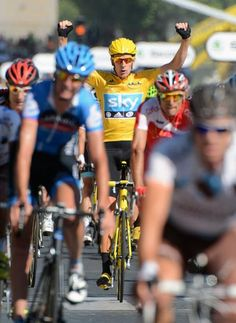 History in the making: Bradley Wiggins (Sky) crosses the finish line arms aloft as the first British Tour champion.