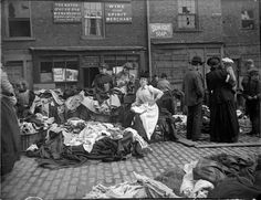 A secondhand clothes seller at Newcastle cloth market reads as customers inspect her goods. A set of original glass negatives showing street scenes of 19th century Newcastle has been found by Aaron Guy, who works at the city's Mining Institute  Photograph: NEMiPA – Collection of the Society of Antiquaries, Newcastle