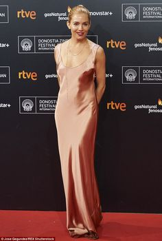 Metallic: The British beauty donned a scoop-neck, copper satin Galvan gown which skimmed h...