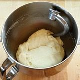 The dough is kneaded and ready when it is smooth, feels slightly tacky, forms a ball without sagging, and springs back when poked.
