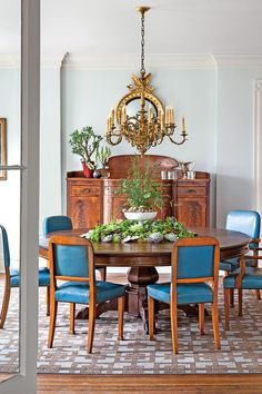 The Dining Room - Charming Lexington Historic Home - Southernliving. The dining room's pale blue walls are painted Sherwin-Williams' Aqua Pura. After lots of searching, Jon found the 7-foot round table in a favorite antiques shop in Lambertville, New Jersey. Made in 1872, it came out of a Philadelphia hunt club. The 1950s dining chairs probably came from an office boardroom. The blue-and-chocolate Stark carpet was custom made for the space.