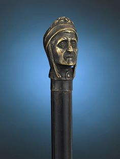 "The likeness of literary legend Dante Alighieri tops this intriguing walking stick. Often referred to as ""il Sommo Poeta"" or ""the Supreme Poet"", the Italian author composed his magnum opus,<em> The Divine Comedy</em> between 1309-1320. Today, this epic poem is considered by many scholars to be a masterpiece of world literature. The intricate metal handle resides atop an ebonized wood shaft.<br><br>35 1/2"" length"