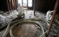 Juan Leon (left) and Evelino Sanchez, working in a crew for Insulation Technologies, also known as Intec, blow cellulose insulation into the attic of a home in the 2000 block of N. 49th St. in Milwaukee.